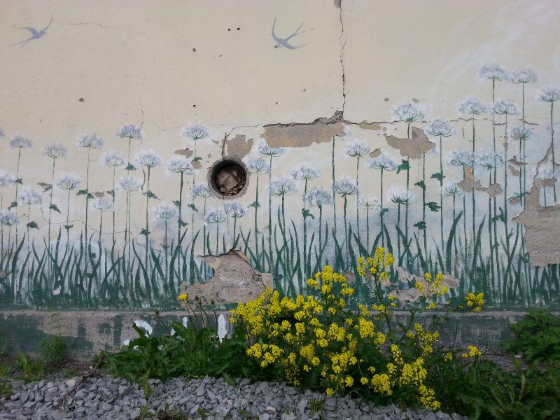 Vaikka maali on jo rapistunut, talon kadulta katsottuna oikeasta seinustasta voi lähemmässä tarkastelussa erottaa taiteellisen kädenjäljen.