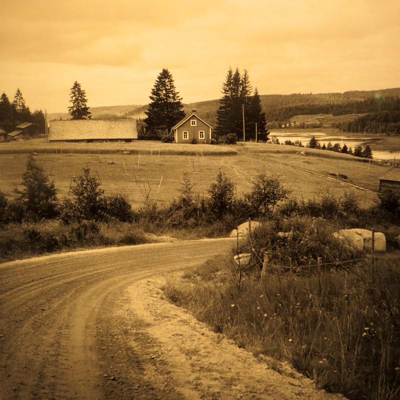 Hirsiset talot rakennettiin usein mäelle, ympärillä pellot ja hiekkatiet.