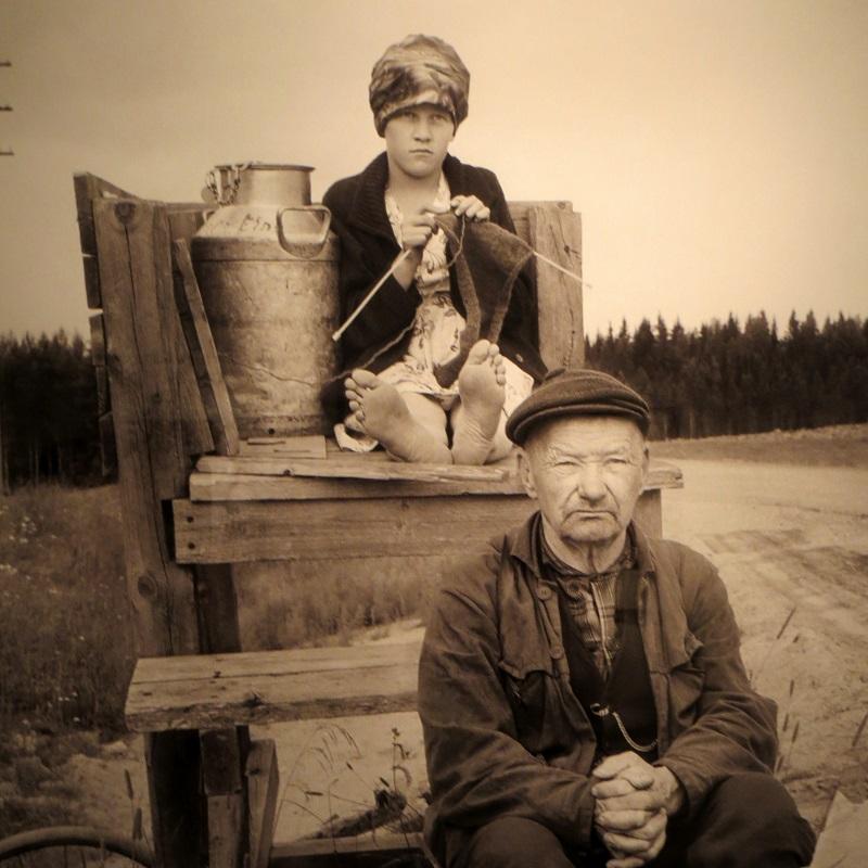 Kuva otettu Pohjois-Savosta. Ahkera tyttö kutoo villapaitaa, odottaa isän kanssa postia ja Savon Sanomia.