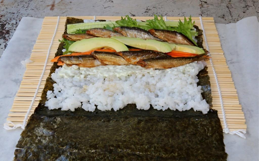 Sushiburrito täytettynä, käärimistä vaille valmis. Sushimatto helpottaa käärimistä, mutta se onnistuu voipaperinkin avulla.