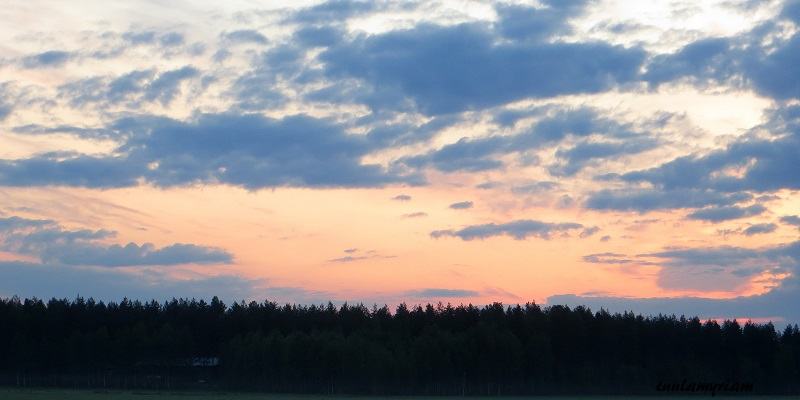 Aurinko punertaa jo, taivaalla on pilviä.