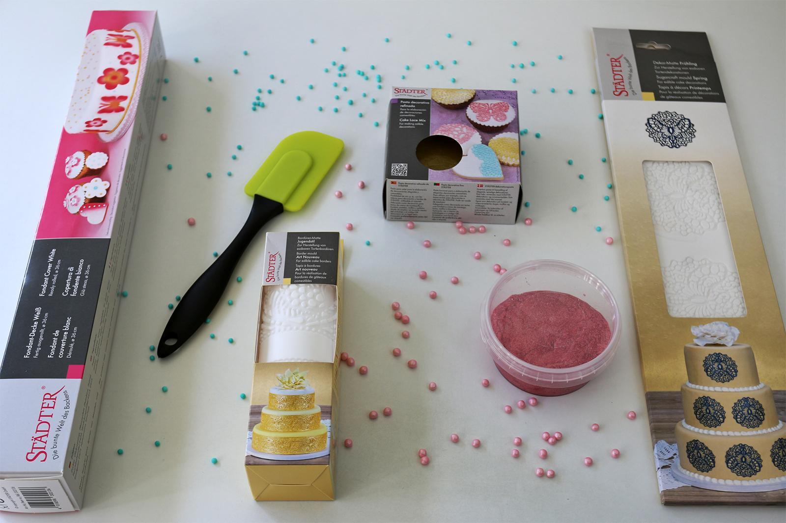 Tuotteet vasemmalta alkaen. Valmiiksi kaulittu sokerimassarulla (Fondant Cover white), silikoninen reunakoristematto (jugend), keltainen ja vaaleanpunainen Edel-koristetahna, silikoninen koristematto (kevät). Kaikki Städter-merkkisiä.