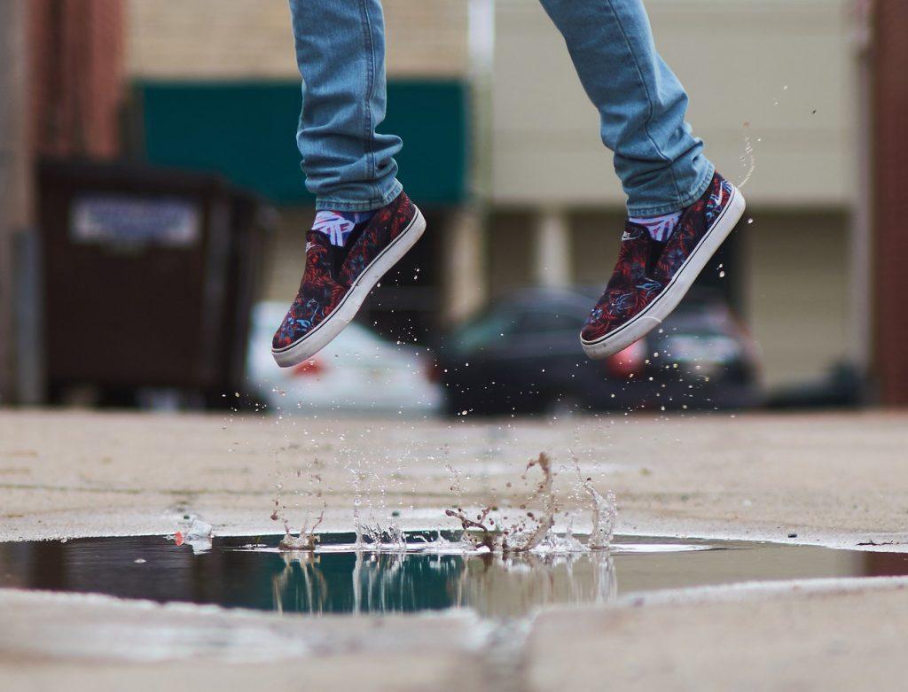 Nuori hyppää vesilätäköstä ja vesi pärskyy.