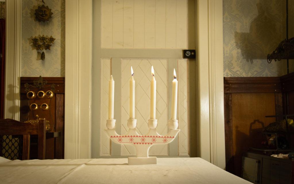 Kynttelikössä palaa kolme kynttilää. Kuvattu vanhan hirsitalon tuvassa.