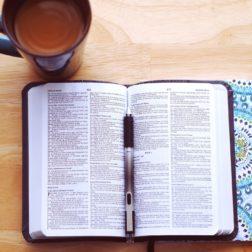 Auki oleva raamattu ja kahvikuppi.