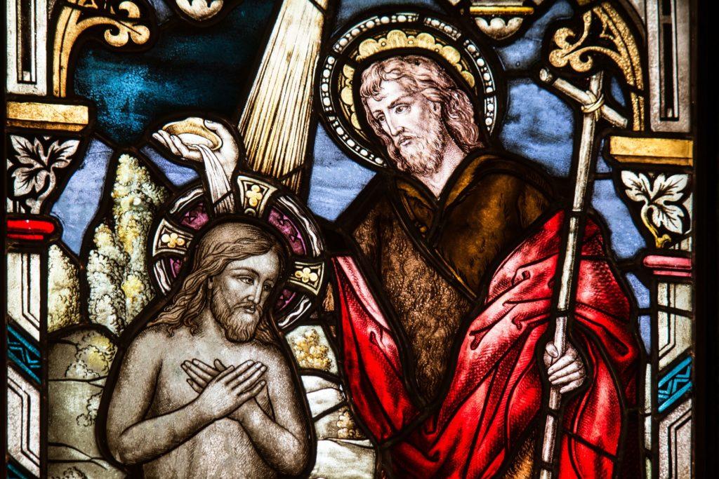 Lasimaalaus, jossa Johannes Kastaja kastaa Jeesuksen.